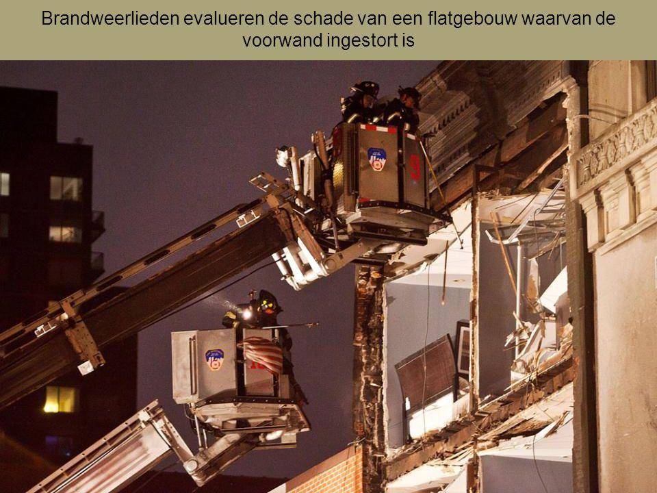Brandweerlieden evalueren de schade van een flatgebouw waarvan de