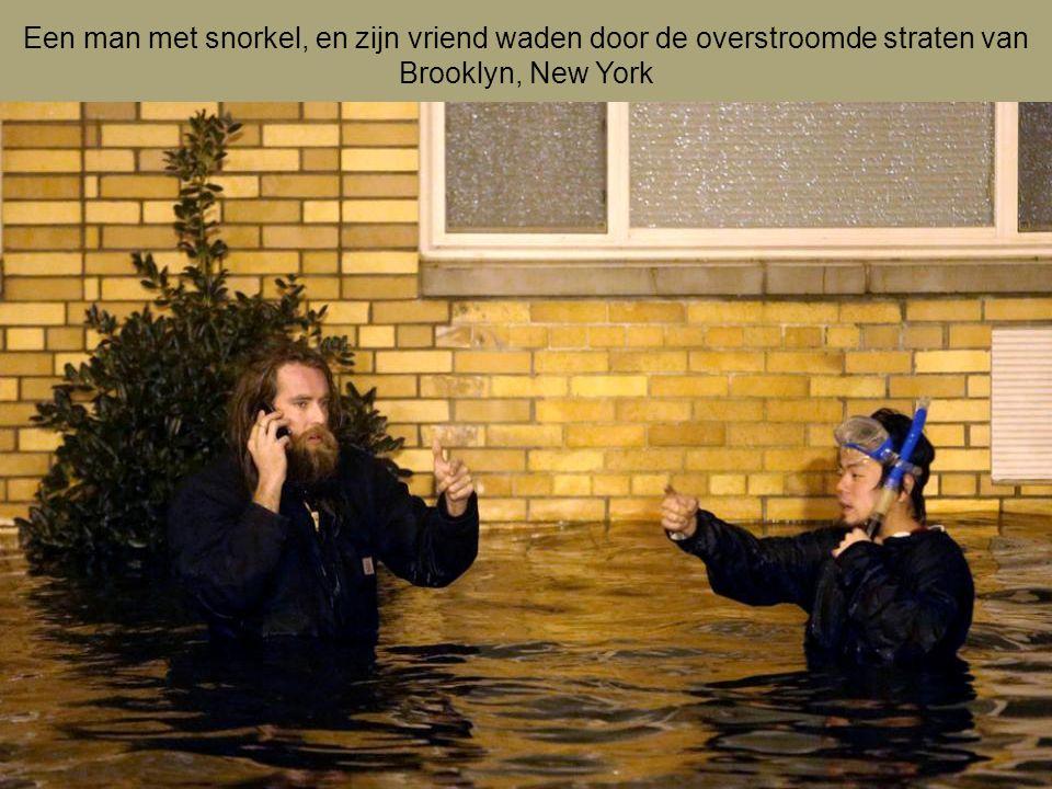 Een man met snorkel, en zijn vriend waden door de overstroomde straten van Brooklyn, New York