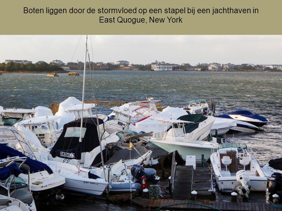 Boten liggen door de stormvloed op een stapel bij een jachthaven in