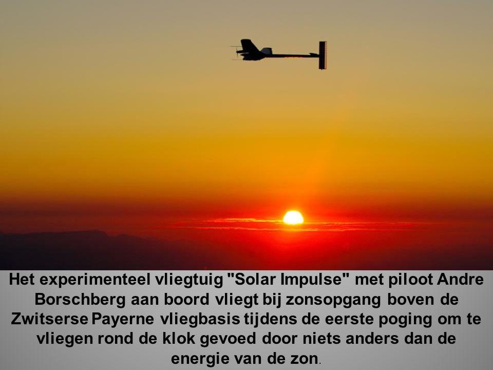 Het experimenteel vliegtuig Solar Impulse met piloot Andre Borschberg aan boord vliegt bij zonsopgang boven de Zwitserse Payerne vliegbasis tijdens de eerste poging om te vliegen rond de klok gevoed door niets anders dan de energie van de zon.