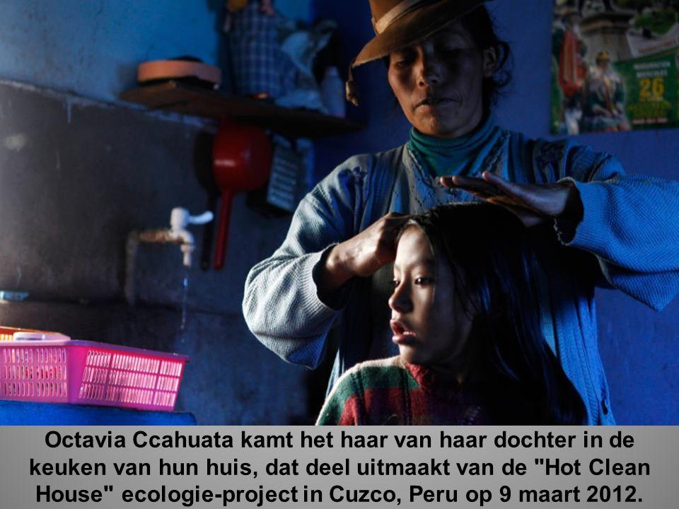 Octavia Ccahuata kamt het haar van haar dochter in de keuken van hun huis, dat deel uitmaakt van de Hot Clean House ecologie-project in Cuzco, Peru op 9 maart 2012.