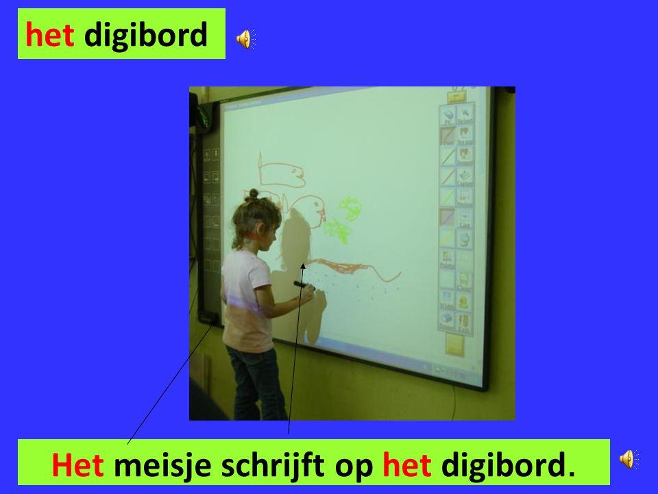 Het meisje schrijft op het digibord.