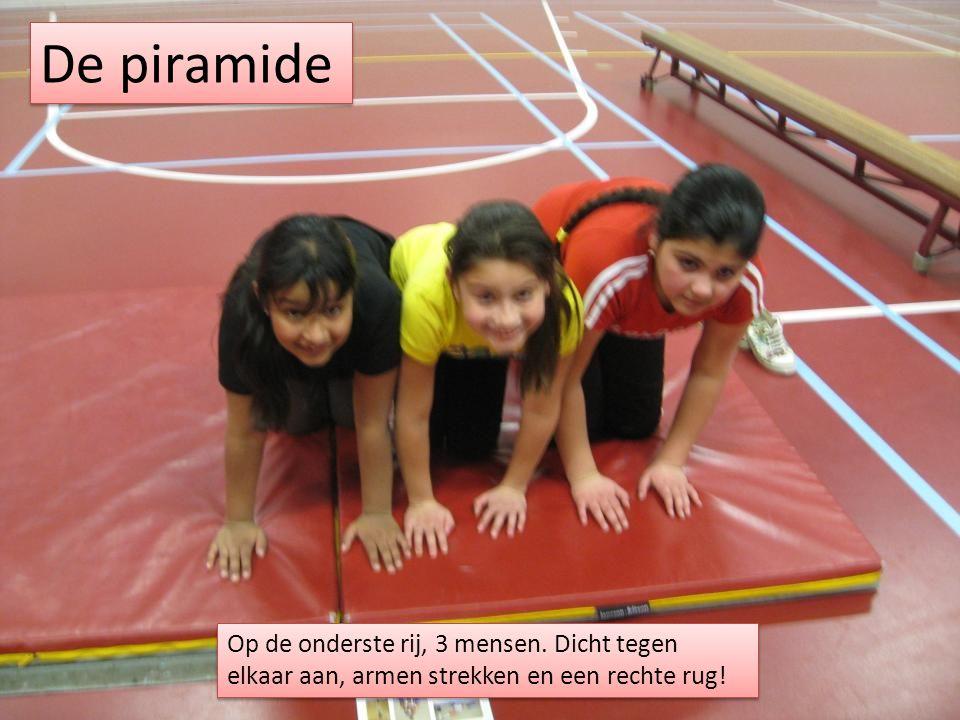 De piramide Op de onderste rij, 3 mensen. Dicht tegen elkaar aan, armen strekken en een rechte rug!