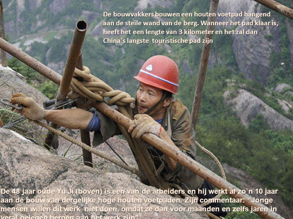 De bouwvakkers bouwen een houten voetpad hangend aan de steile wand van de berg. Wanneer het pad klaar is, heeft het een lengte van 3 kilometer en het zal dan China`s langste touristische pad zijn