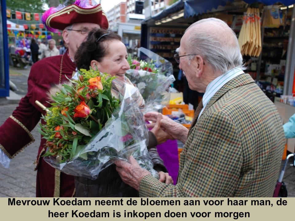 Mevrouw Koedam neemt de bloemen aan voor haar man, de