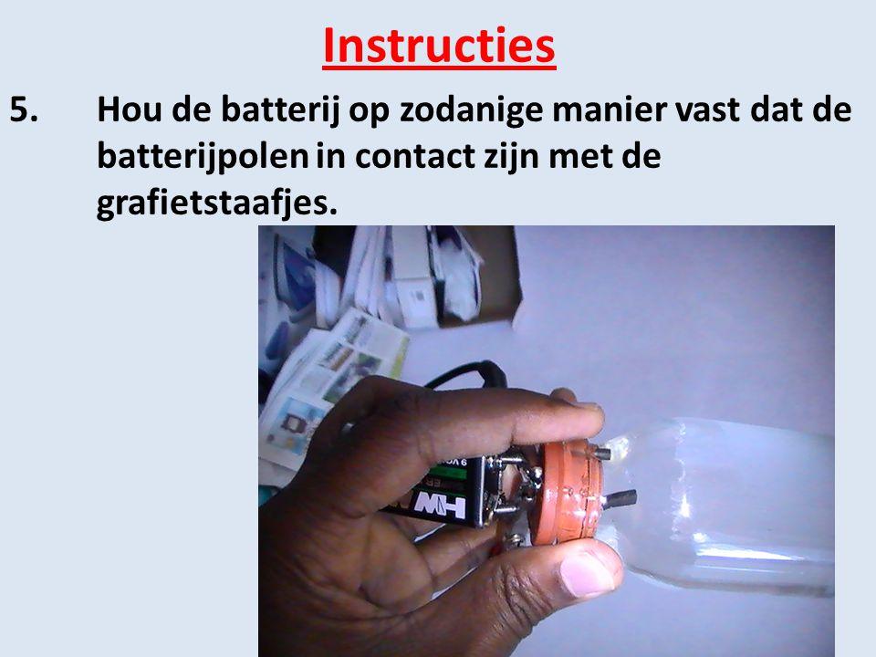 Instructies 5. Hou de batterij op zodanige manier vast dat de batterijpolen in contact zijn met de grafietstaafjes.