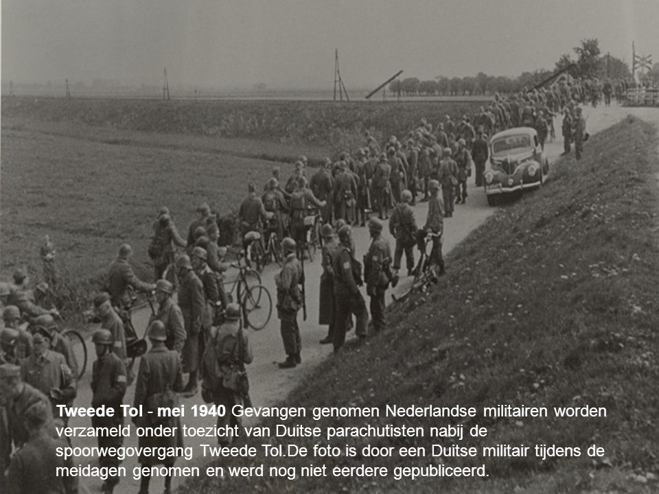 Tweede Tol - mei 1940 Gevangen genomen Nederlandse militairen worden verzameld onder toezicht van Duitse parachutisten nabij de spoorwegovergang Tweede Tol.De foto is door een Duitse militair tijdens de meidagen genomen en werd nog niet eerdere gepubliceerd.