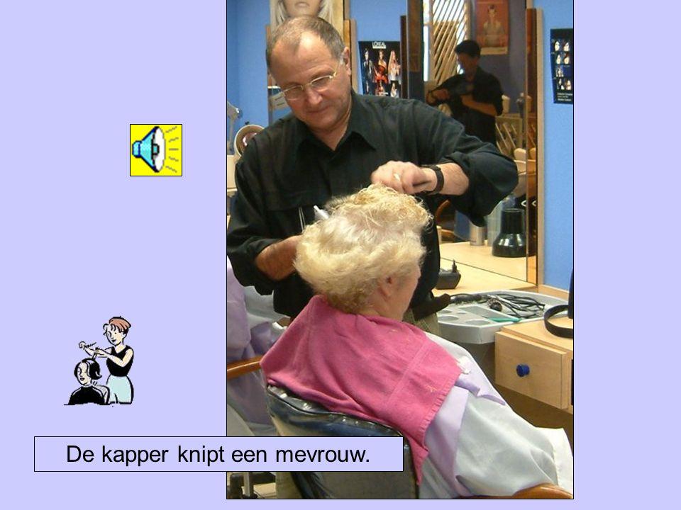 De kapper knipt een mevrouw.