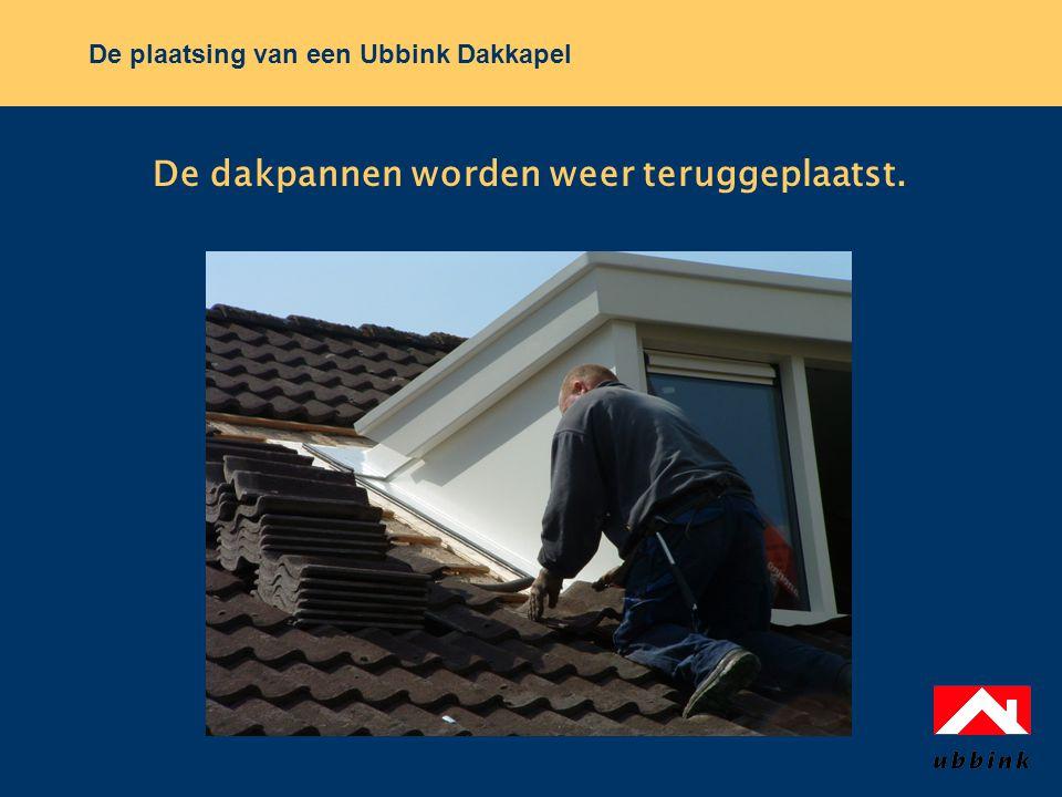 De dakpannen worden weer teruggeplaatst.