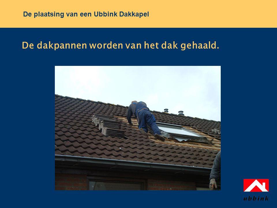 De dakpannen worden van het dak gehaald.