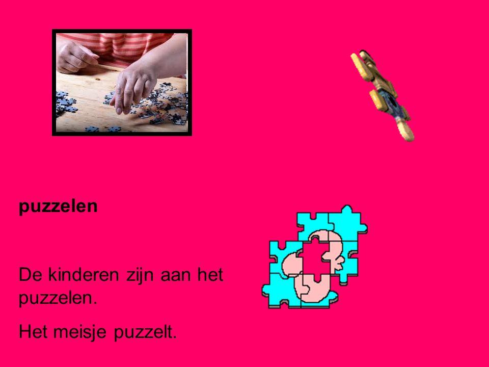puzzelen De kinderen zijn aan het puzzelen. Het meisje puzzelt.
