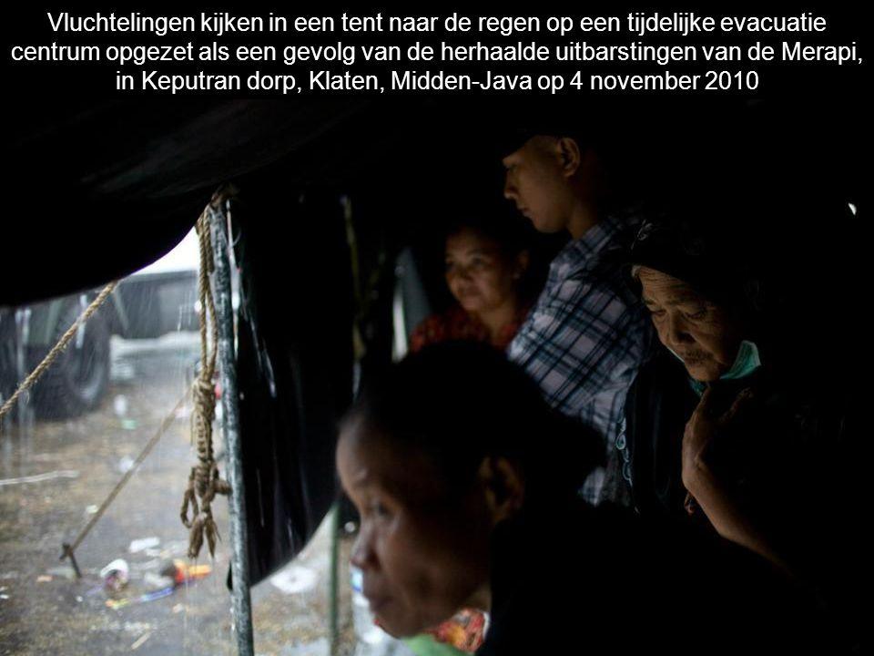 Vluchtelingen kijken in een tent naar de regen op een tijdelijke evacuatie centrum opgezet als een gevolg van de herhaalde uitbarstingen van de Merapi, in Keputran dorp, Klaten, Midden-Java op 4 november 2010