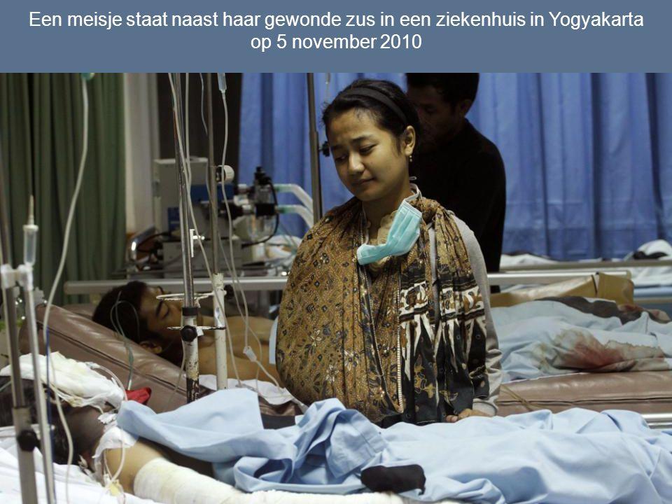Een meisje staat naast haar gewonde zus in een ziekenhuis in Yogyakarta