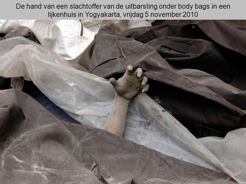 De hand van een slachtoffer van de uitbarsting onder body bags in een lijkenhuis in Yogyakarta, vrijdag 5 november 2010