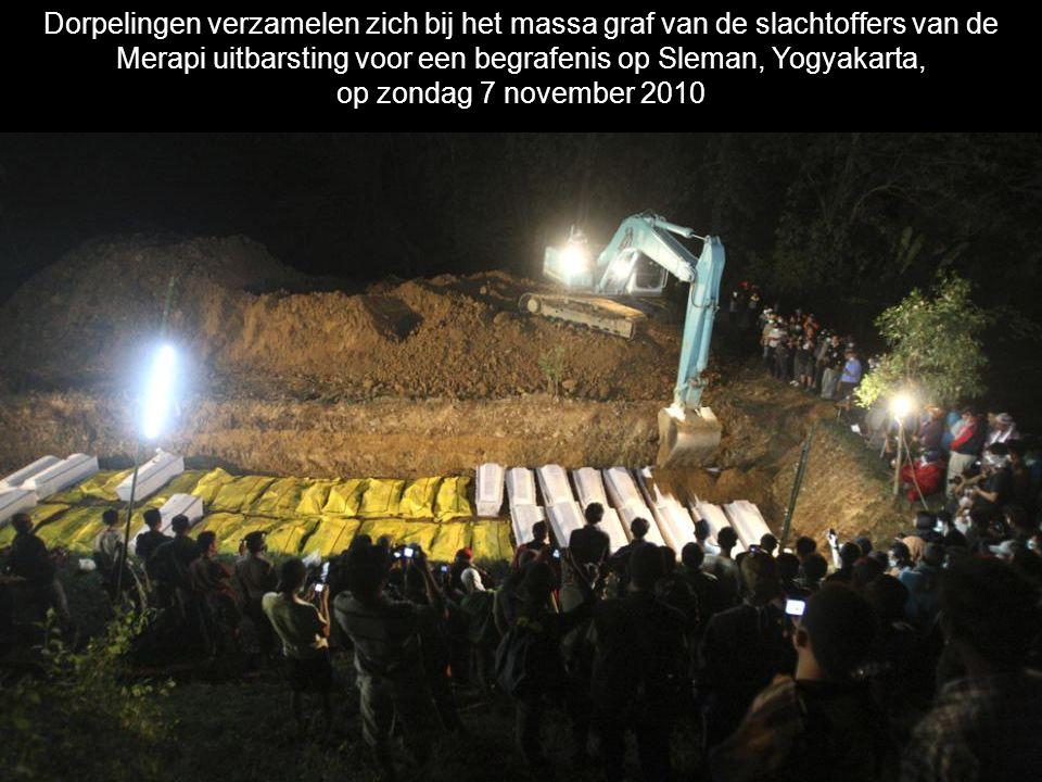 Dorpelingen verzamelen zich bij het massa graf van de slachtoffers van de Merapi uitbarsting voor een begrafenis op Sleman, Yogyakarta,