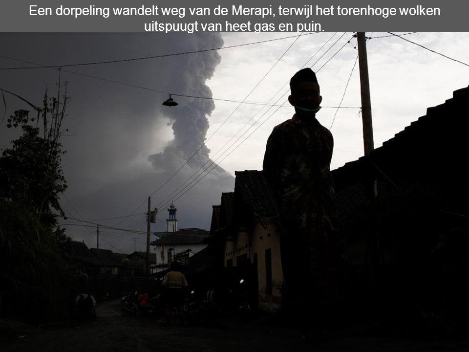 Een dorpeling wandelt weg van de Merapi, terwijl het torenhoge wolken uitspuugt van heet gas en puin.