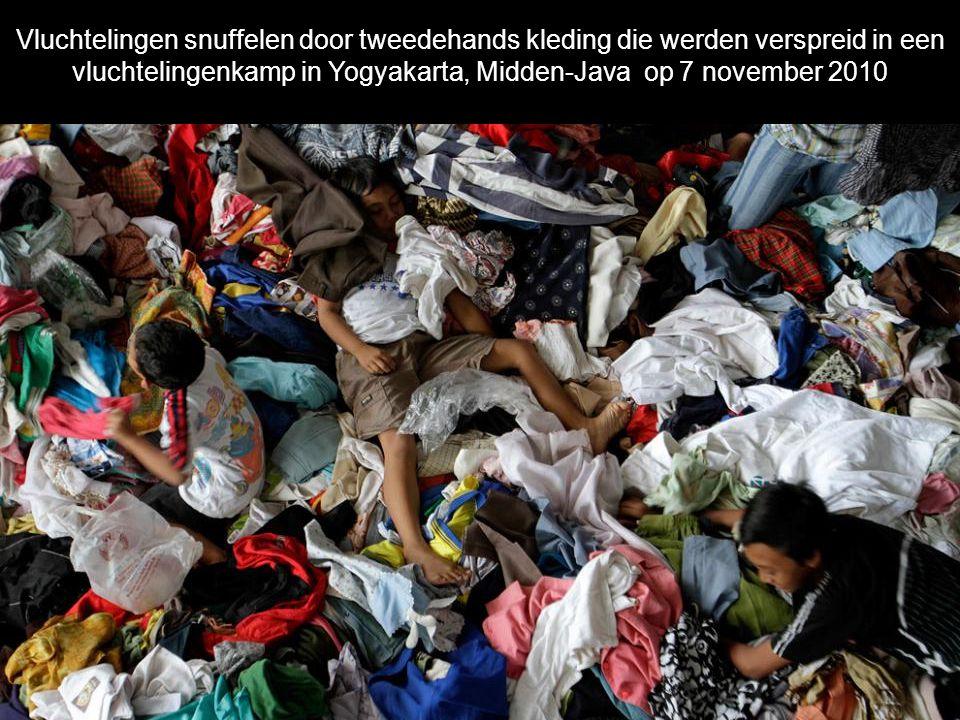 Vluchtelingen snuffelen door tweedehands kleding die werden verspreid in een vluchtelingenkamp in Yogyakarta, Midden-Java op 7 november 2010