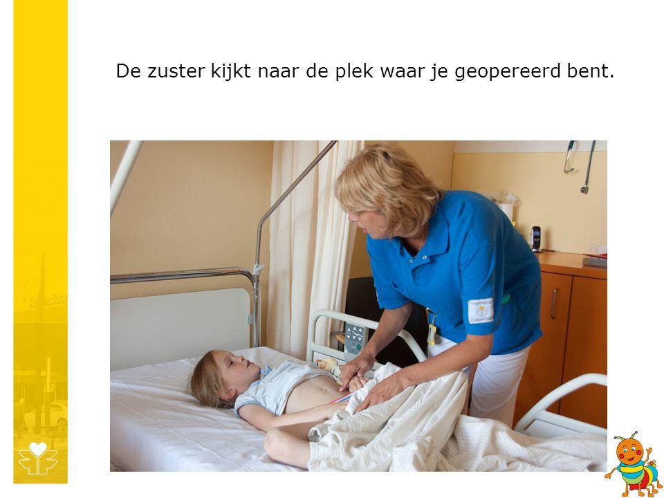 De zuster kijkt naar de plek waar je geopereerd bent.