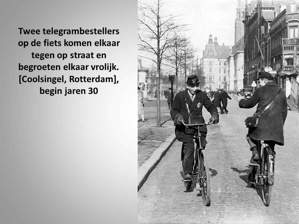 Twee telegrambestellers op de fiets komen elkaar tegen op straat en begroeten elkaar vrolijk.