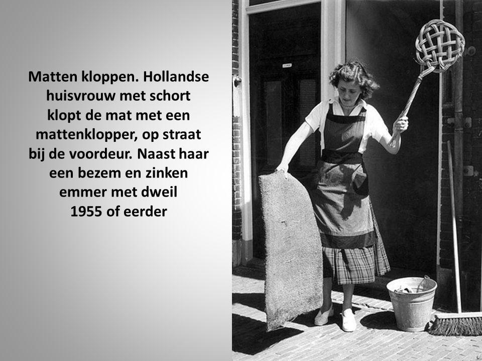 Matten kloppen. Hollandse huisvrouw met schort klopt de mat met een mattenklopper, op straat bij de voordeur. Naast haar een bezem en zinken emmer met dweil