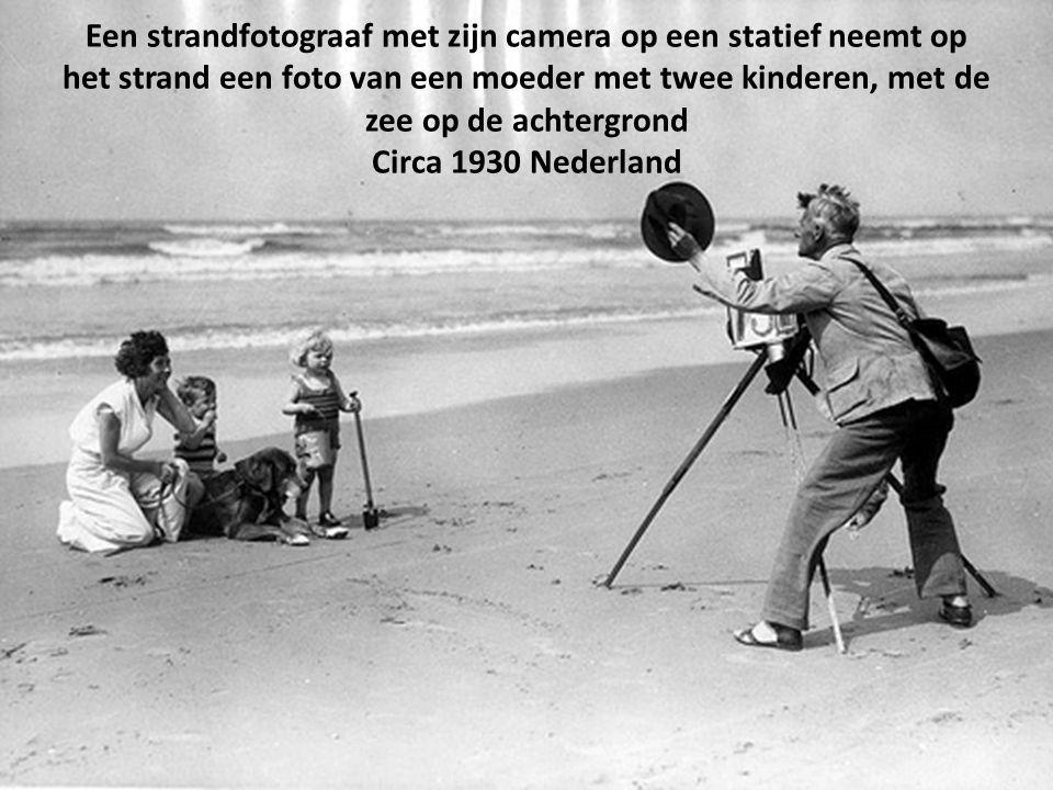 Een strandfotograaf met zijn camera op een statief neemt op het strand een foto van een moeder met twee kinderen, met de zee op de achtergrond