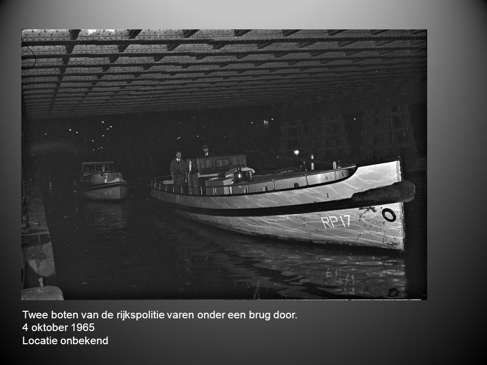 Twee boten van de rijkspolitie varen onder een brug door.