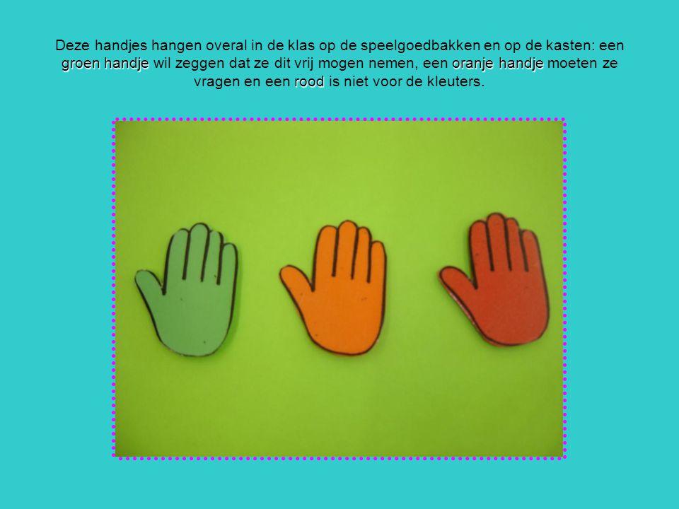 Deze handjes hangen overal in de klas op de speelgoedbakken en op de kasten: een groen handje wil zeggen dat ze dit vrij mogen nemen, een oranje handje moeten ze vragen en een rood is niet voor de kleuters.