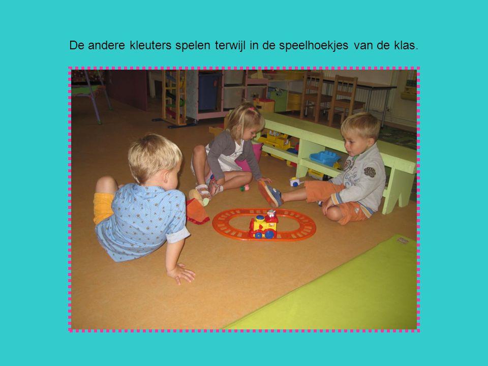 De andere kleuters spelen terwijl in de speelhoekjes van de klas.