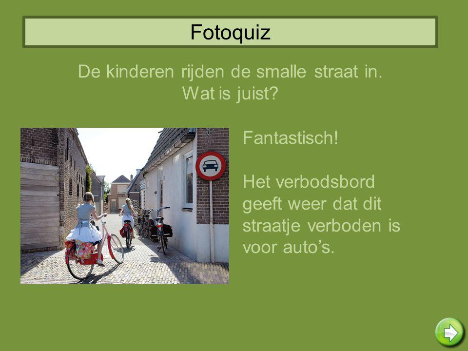 De kinderen rijden de smalle straat in.