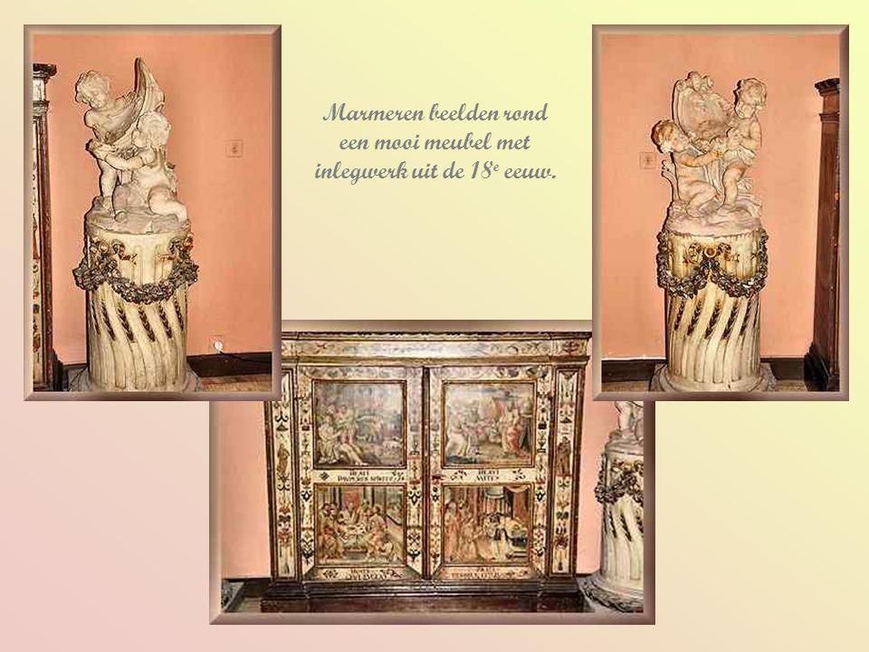 Marmeren beelden rond een mooi meubel met inlegwerk uit de 18e eeuw.