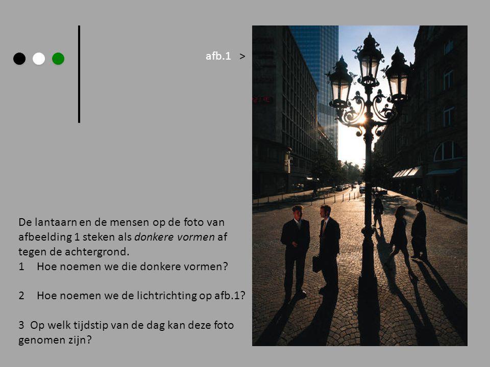 afb.1 > De lantaarn en de mensen op de foto van. afbeelding 1 steken als donkere vormen af. tegen de achtergrond.