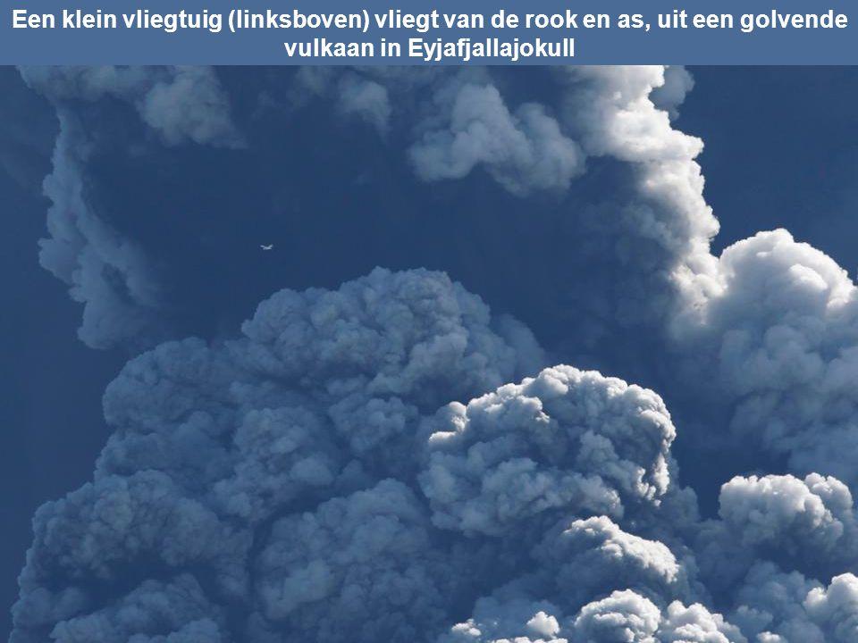 Een klein vliegtuig (linksboven) vliegt van de rook en as, uit een golvende vulkaan in Eyjafjallajokull