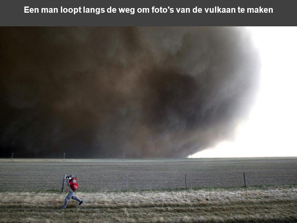 Een man loopt langs de weg om foto s van de vulkaan te maken