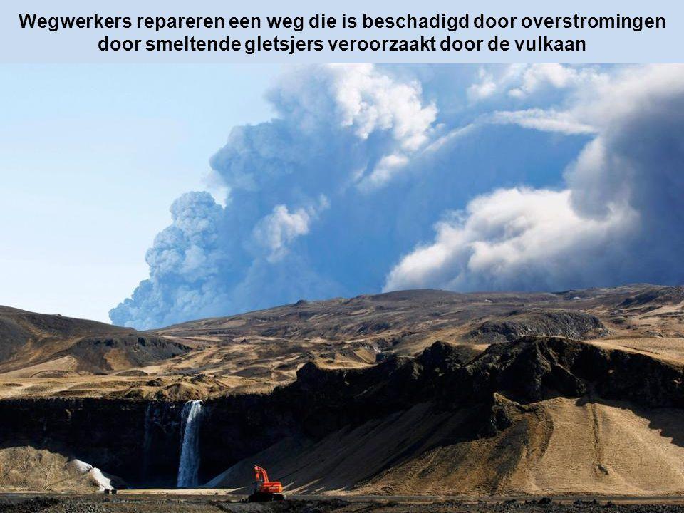 Wegwerkers repareren een weg die is beschadigd door overstromingen door smeltende gletsjers veroorzaakt door de vulkaan