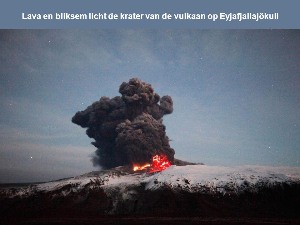 Lava en bliksem licht de krater van de vulkaan op Eyjafjallajökull