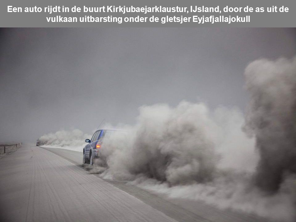 Een auto rijdt in de buurt Kirkjubaejarklaustur, IJsland, door de as uit de vulkaan uitbarsting onder de gletsjer Eyjafjallajokull