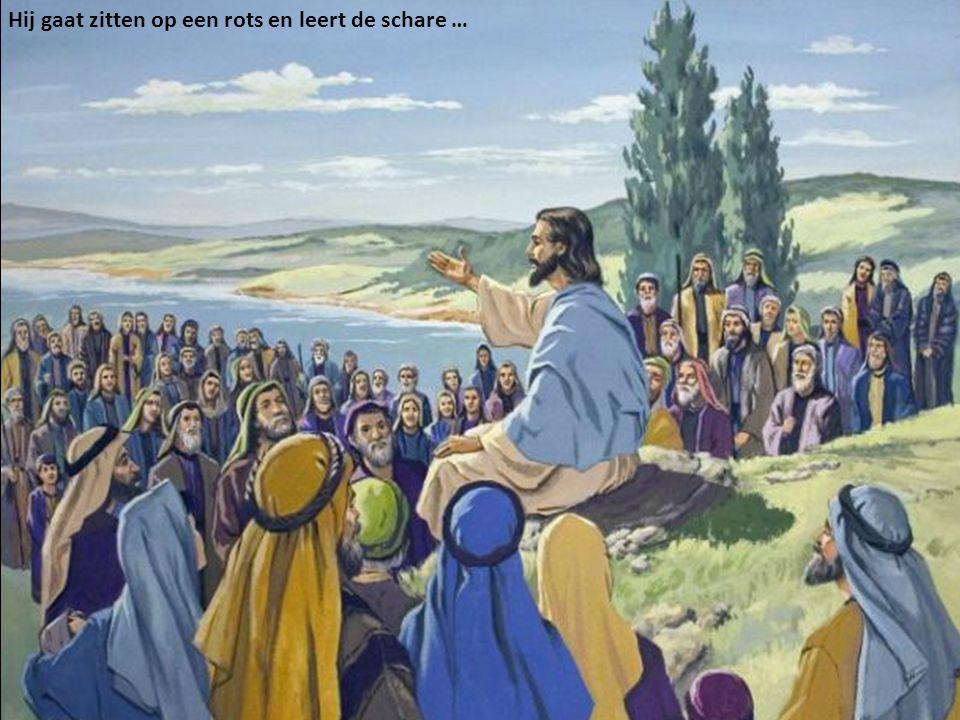 Hij gaat zitten op een rots en leert de schare …