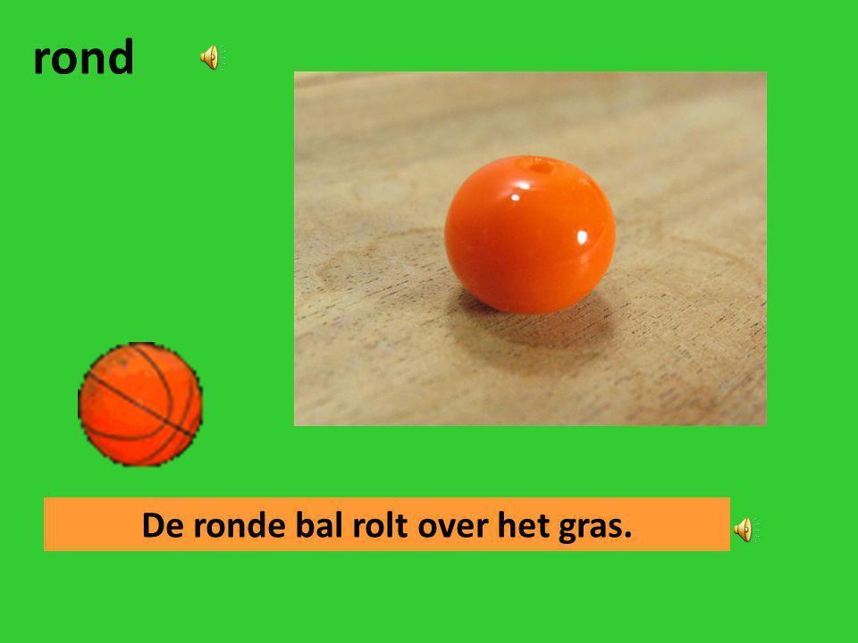 De ronde bal rolt over het gras.