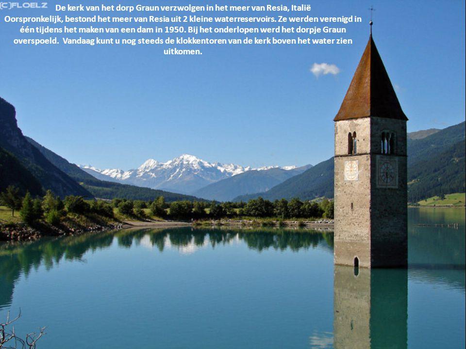 De kerk van het dorp Graun verzwolgen in het meer van Resia, Italië Oorspronkelijk, bestond het meer van Resia uit 2 kleine waterreservoirs. Ze werden verenigd in één tijdens het maken van een dam in 1950. Bij het onderlopen werd het dorpje Graun overspoeld. Vandaag kunt u nog steeds de klokkentoren van de kerk boven het water zien uitkomen.