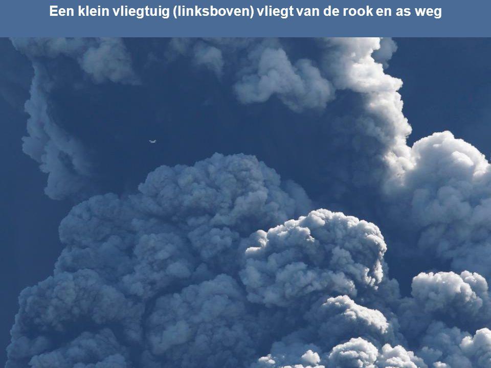 Een klein vliegtuig (linksboven) vliegt van de rook en as weg