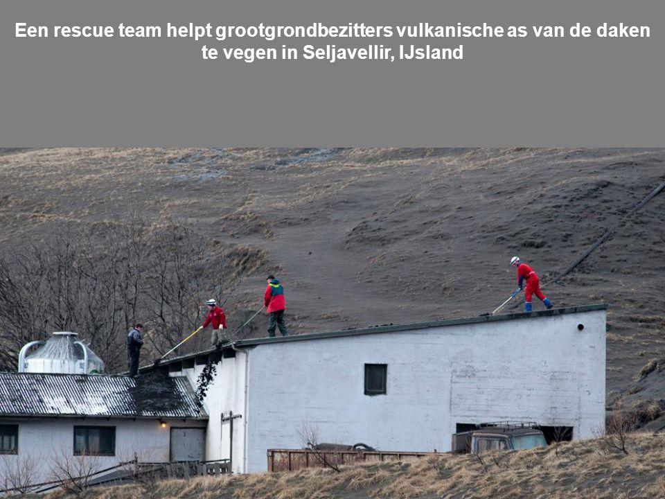 Een rescue team helpt grootgrondbezitters vulkanische as van de daken te vegen in Seljavellir, IJsland