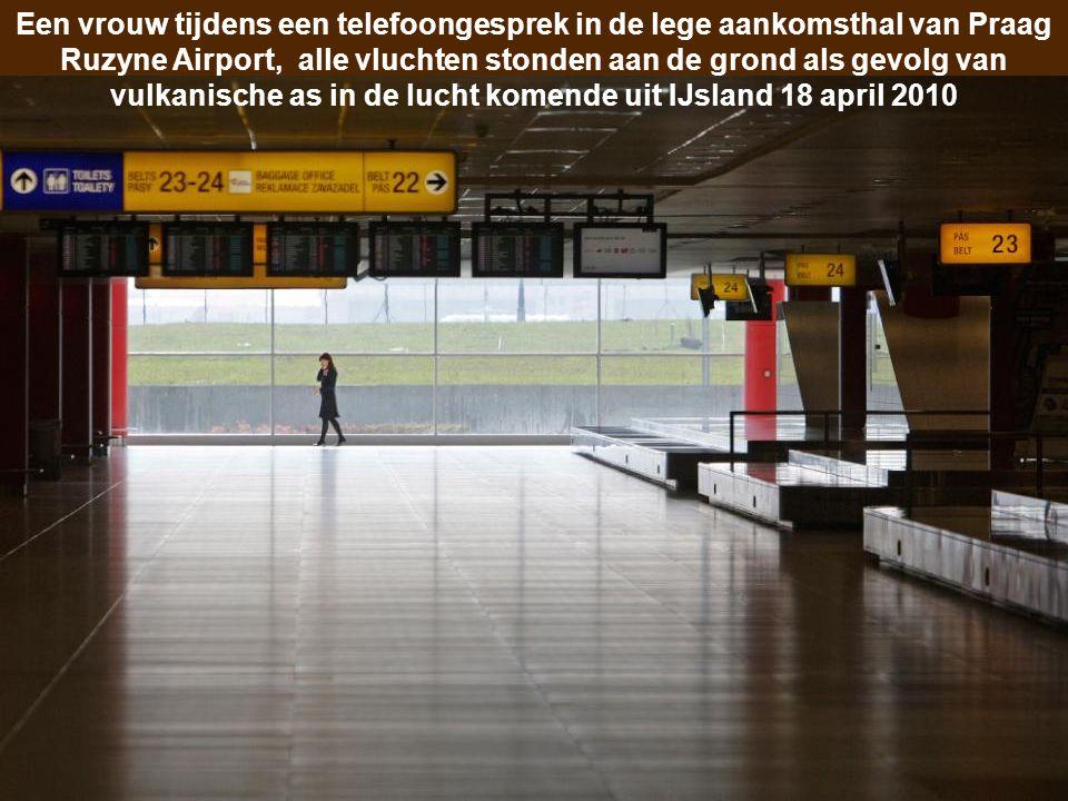 Een vrouw tijdens een telefoongesprek in de lege aankomsthal van Praag Ruzyne Airport, alle vluchten stonden aan de grond als gevolg van vulkanische as in de lucht komende uit IJsland 18 april 2010
