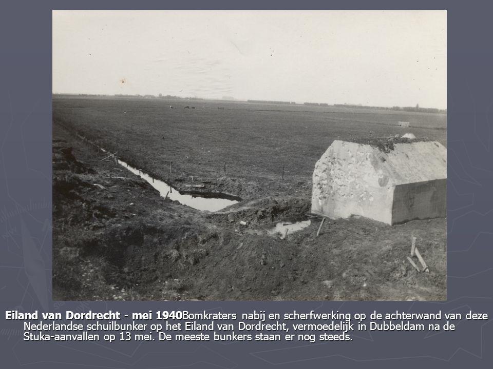 Eiland van Dordrecht - mei 1940Bomkraters nabij en scherfwerking op de achterwand van deze Nederlandse schuilbunker op het Eiland van Dordrecht, vermoedelijk in Dubbeldam na de Stuka-aanvallen op 13 mei.
