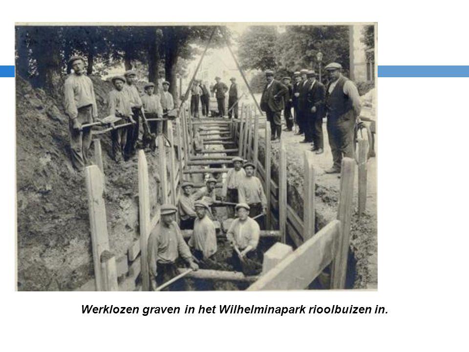 Werklozen graven in het Wilhelminapark rioolbuizen in.