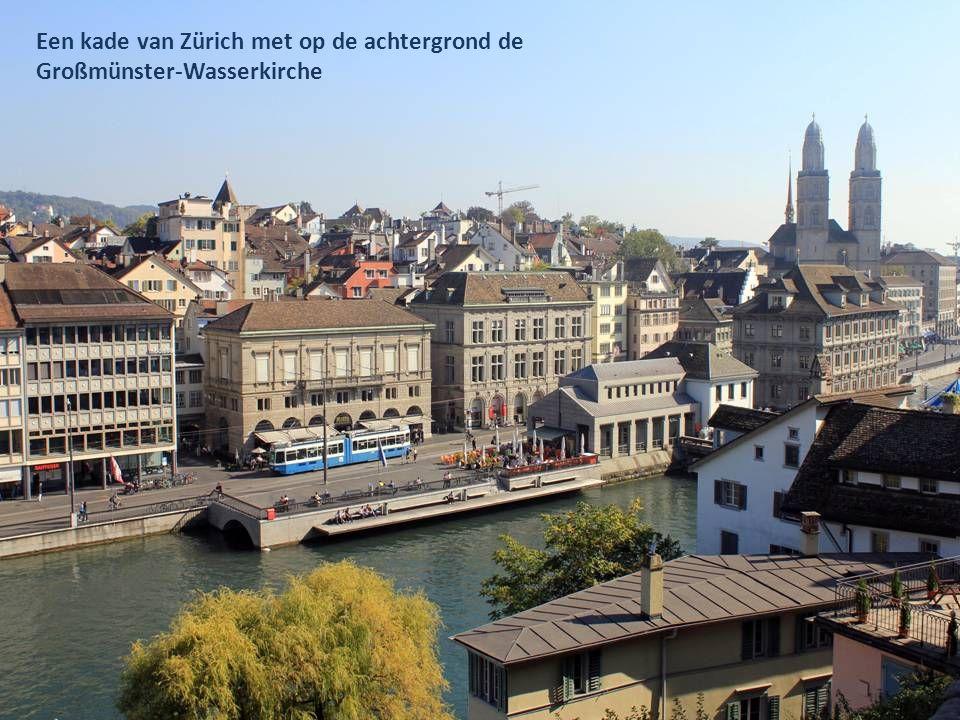 Een kade van Zürich met op de achtergrond de Großmünster-Wasserkirche