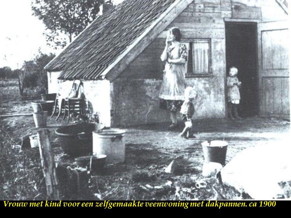 Vrouw met kind voor een zelfgemaakte veenwoning met dakpannen. ca 1900
