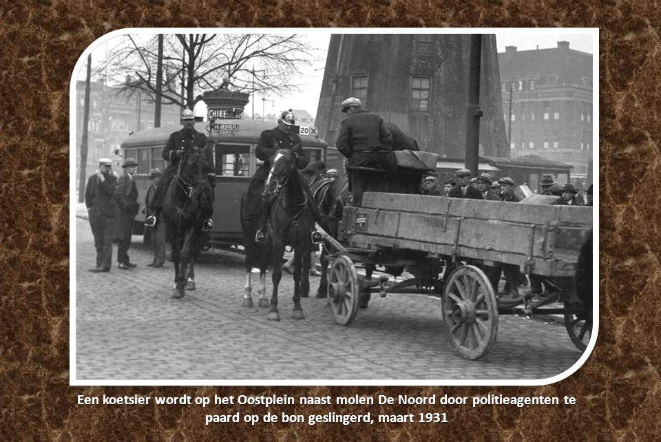 Een koetsier wordt op het Oostplein naast molen De Noord door politieagenten te paard op de bon geslingerd, maart 1931