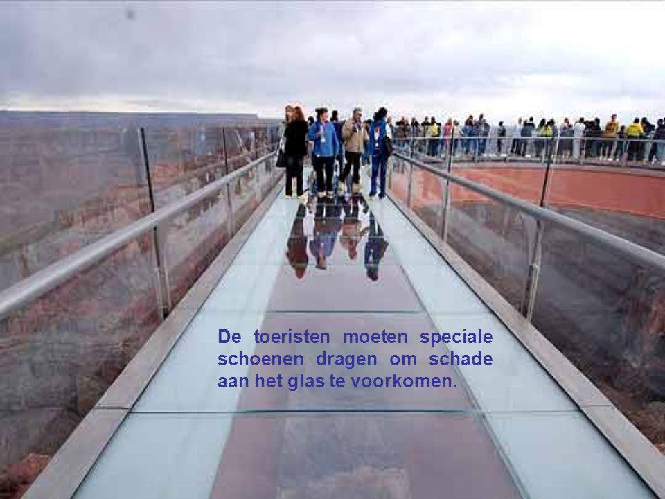 De toeristen moeten speciale schoenen dragen om schade aan het glas te voorkomen.