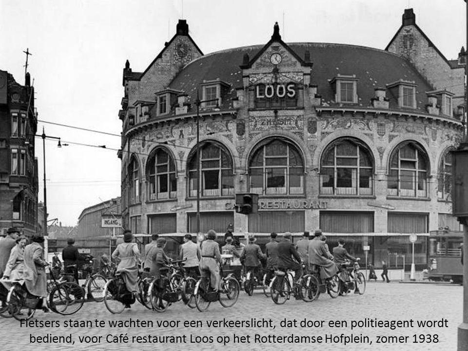 Fietsers staan te wachten voor een verkeerslicht, dat door een politieagent wordt bediend, voor Café restaurant Loos op het Rotterdamse Hofplein, zomer 1938