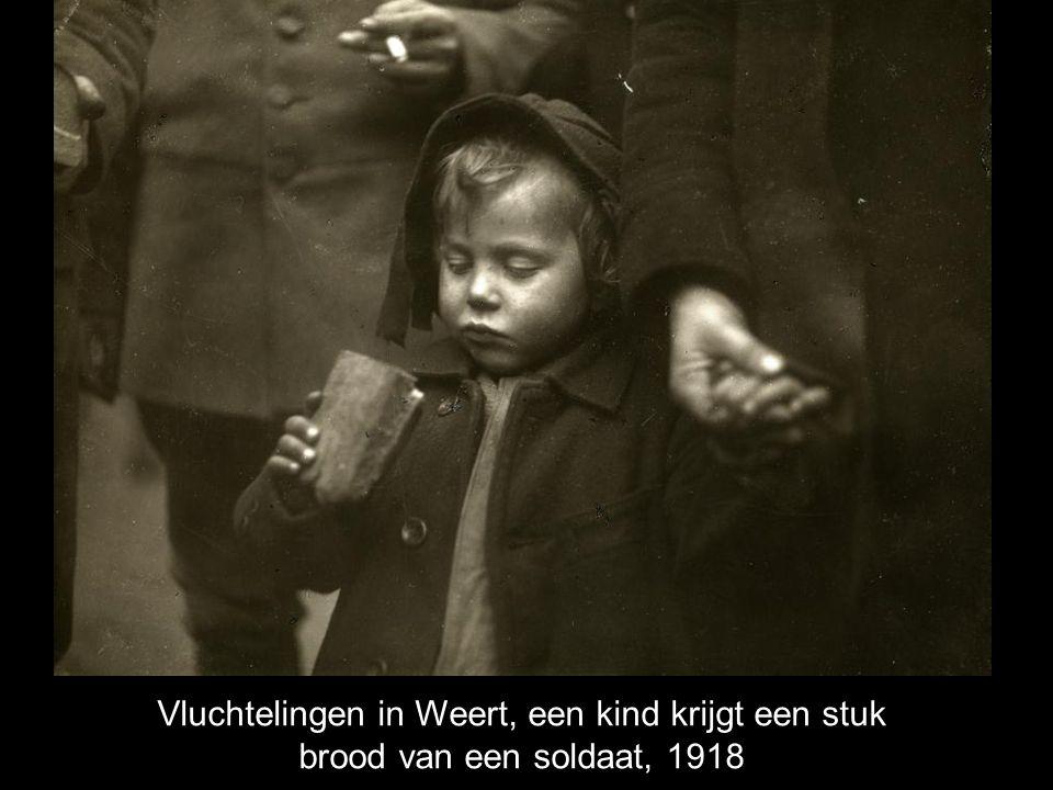 Vluchtelingen in Weert, een kind krijgt een stuk brood van een soldaat, 1918